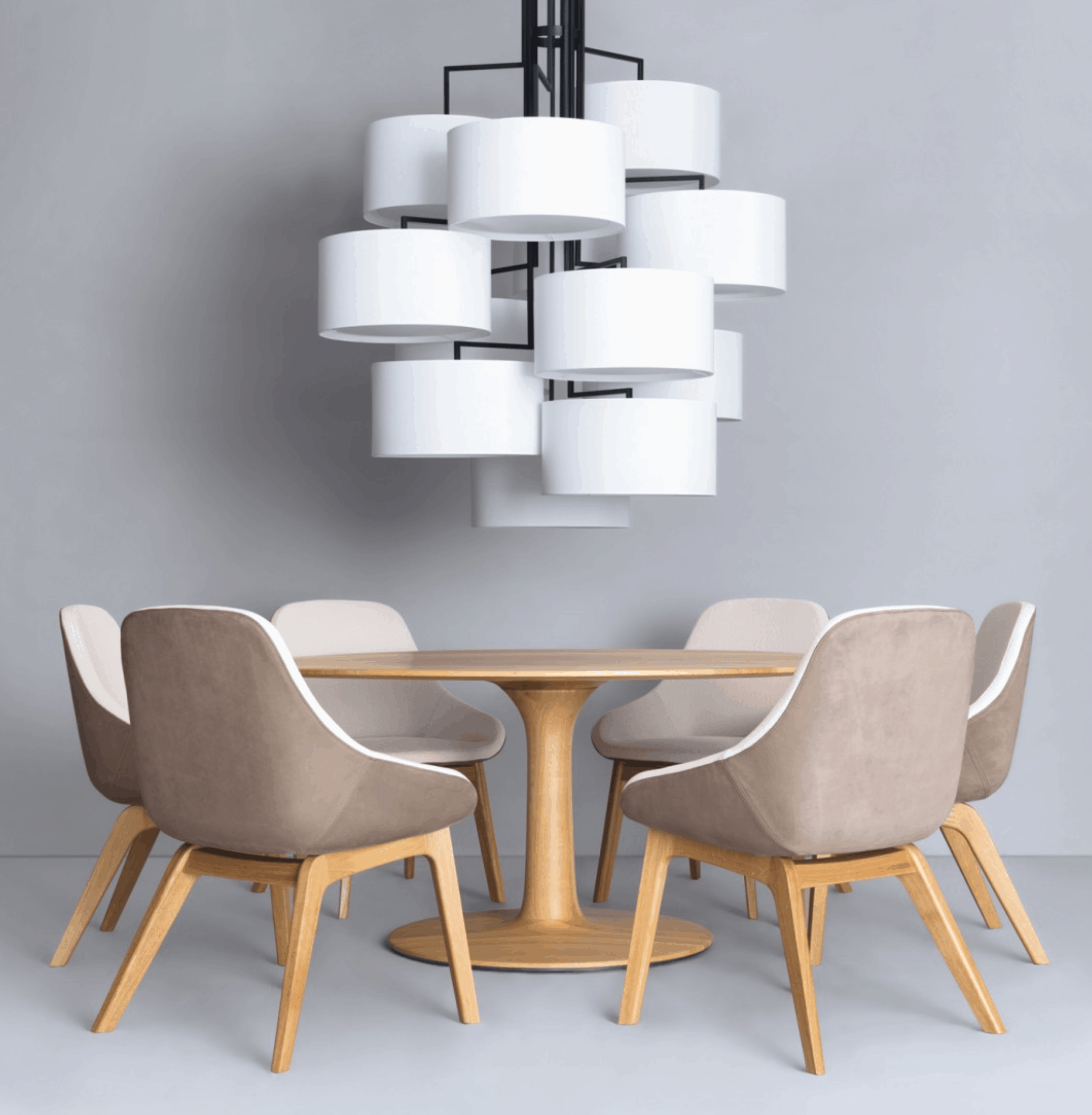 art deco light fixtures with white shades above modern table with gray chairs, wood grain legs