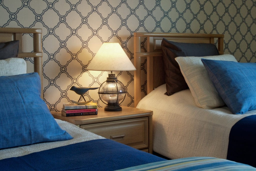 eclectic bedroom with double beds, patterned wallpaper, blue decorative pillows. a lamp and a few books with a decorative bird sit on an endtable between the beds