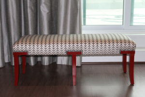 decorative bench with red legs, pattern upholstery, inside room with gray drapes and window