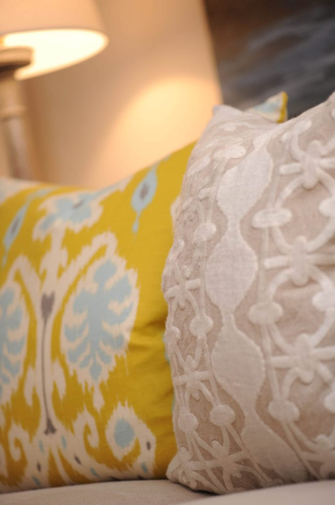 decorative throw pillows with colorful prints, the pillow on the left is yellow with white and blue abstract designs, the pillow on the right is taupe with an intricate white print