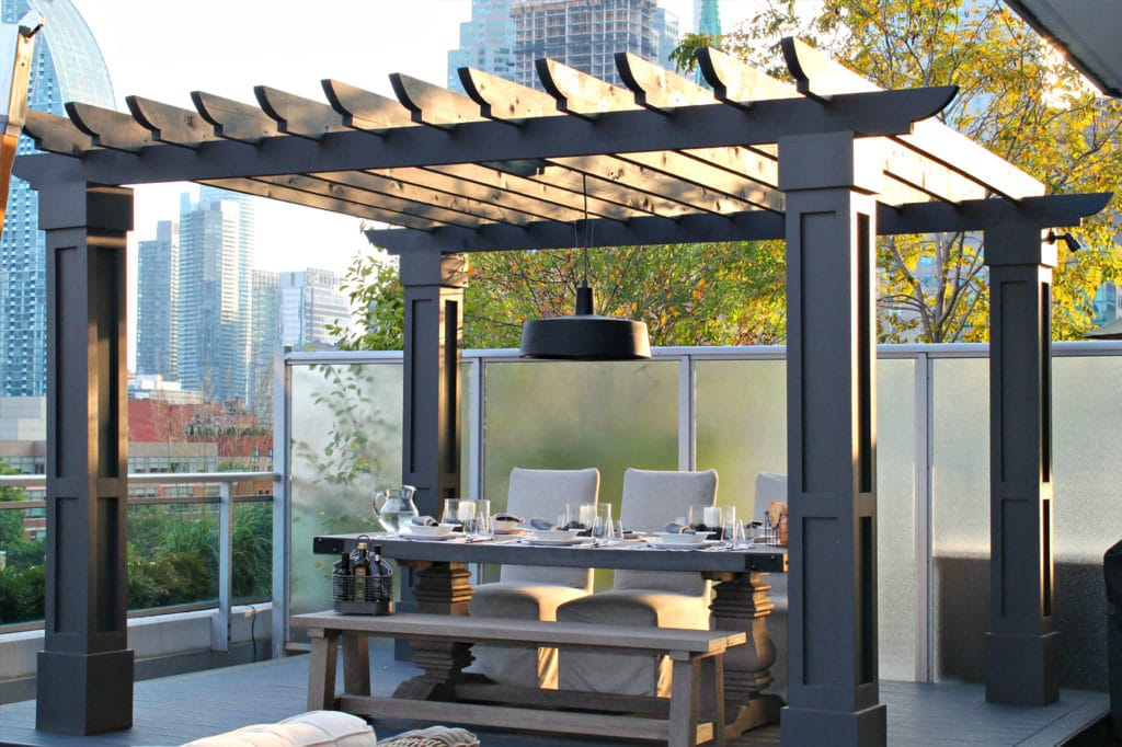 outdoor dining under a pergola in a city setting
