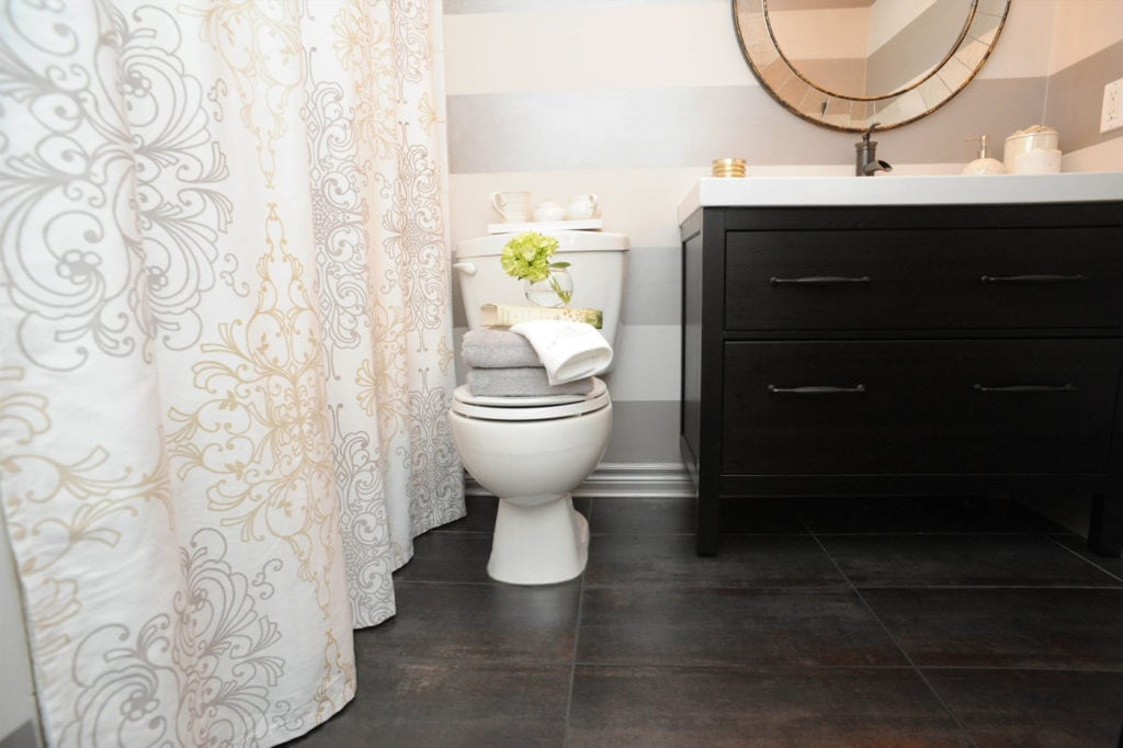 Modern bathroom with dark vanity, and bands of silver paint creating pattern on the wall, and scroll patterned shower curtain. Design by Judith Taylor Designs