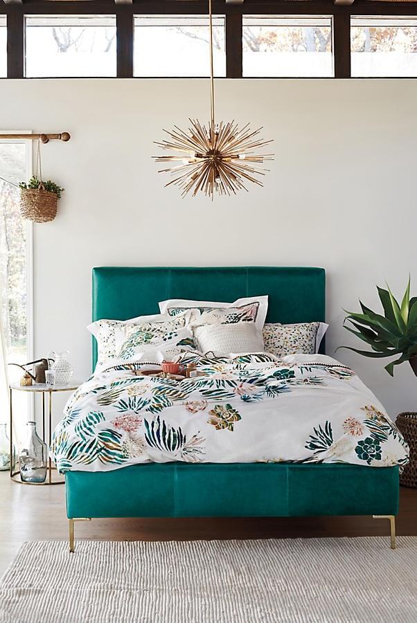white bedroom with gold abstract lighting, blue velvet bedframe, white patterned bedding