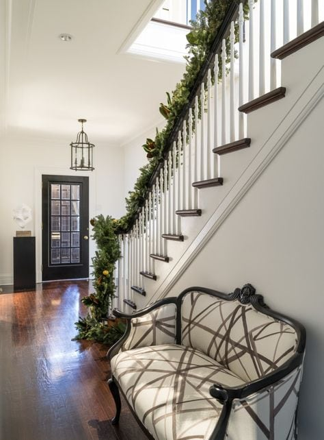 entryway of home, stairs draped in greenery, white patterned loveseat