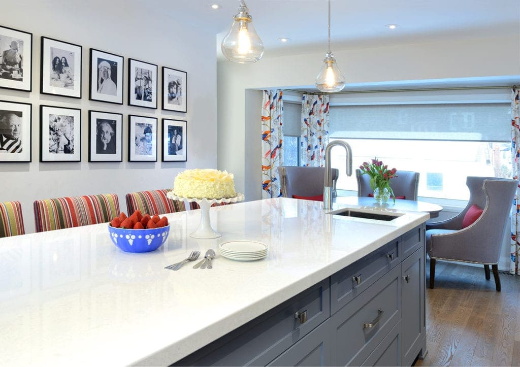 white kitchen countertop on grey cabinets in foreground with black and white framed art on the wall and dining area in the background
