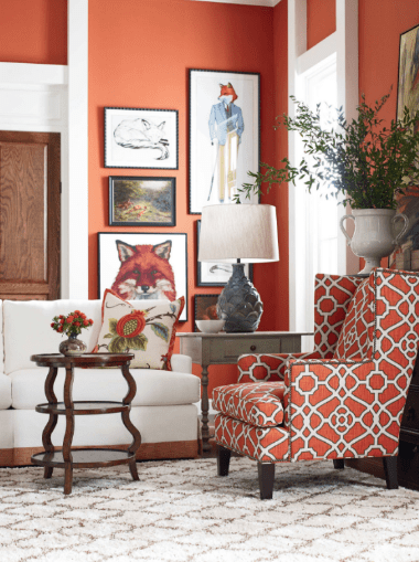 red room with decorative wall art, white patterned rug, red patterned armchair, white couch