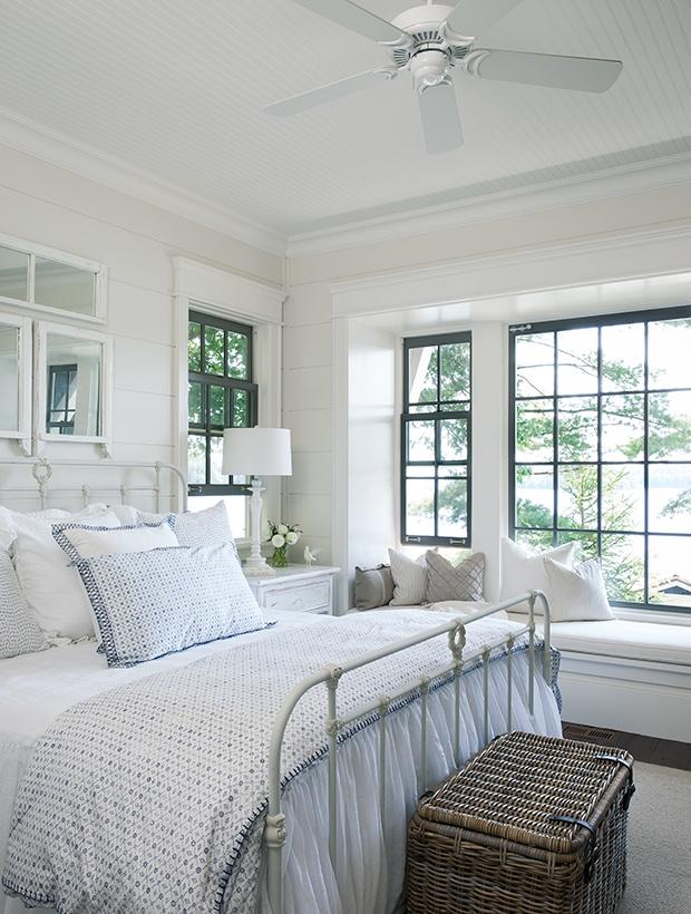 white bedroom, wicker trunk, white bedspread, white ceiling fan