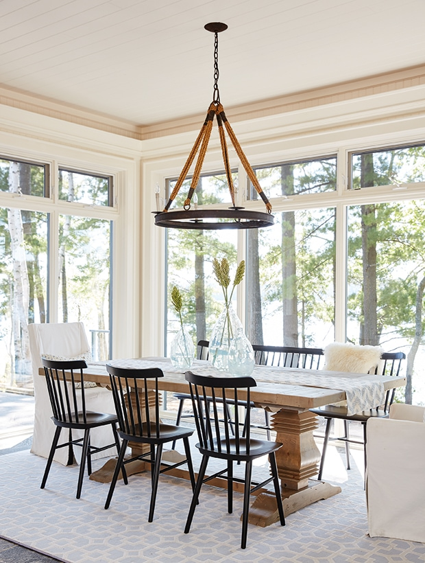 dining area surrounded by windows, rustic light fixture