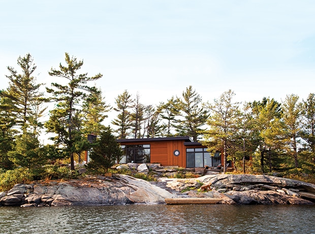 cottage on lake surrounded by trees