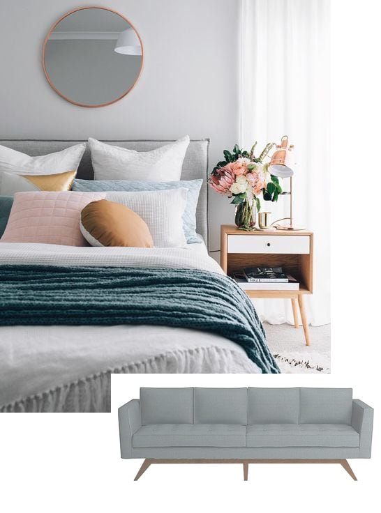 bedroom with gray walls, mirror, white bed with blue throw blanket, deco pillows, white wood grain nightstand with flowers