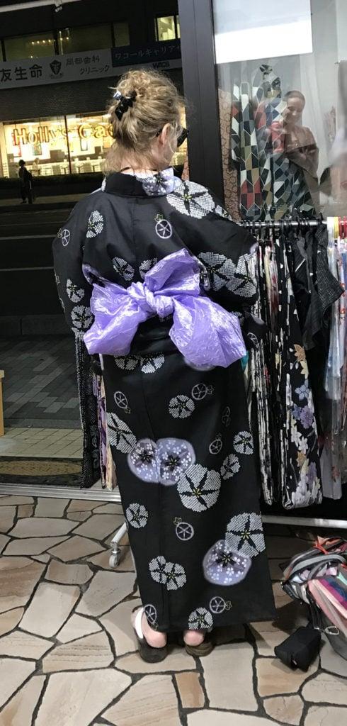 photo of blond girl in a black kimono and purple sash