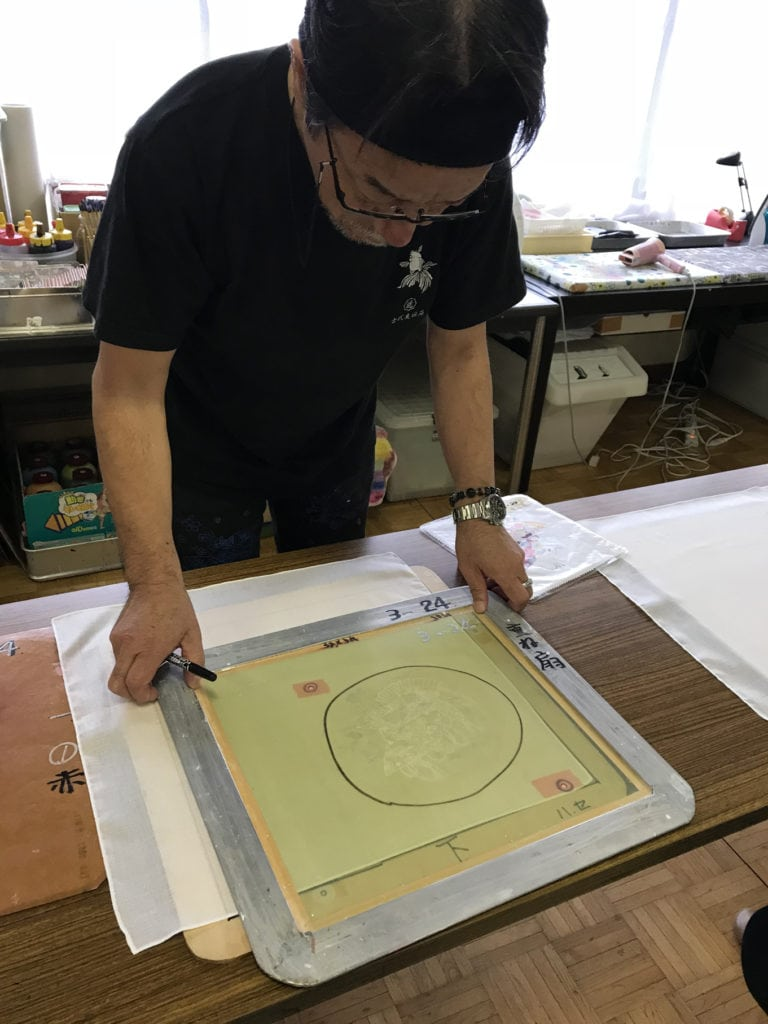 man showing screen printing technique