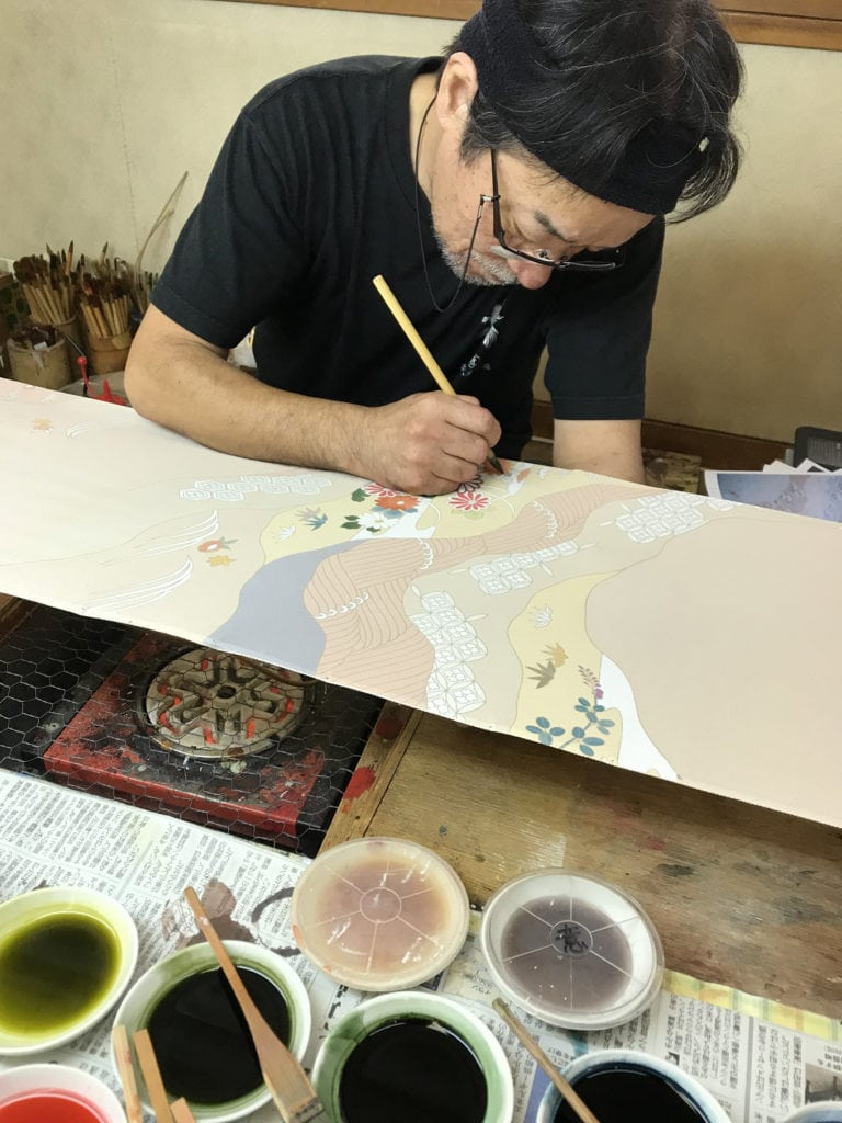 close-up of man painting on silk for kimonos