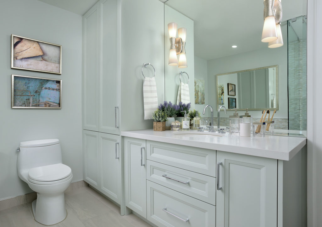 Bathroom shot of aqua cabinet with large mirror with sconces on the mirror, artwork over the toilet. Work by Judith Taylor Designs