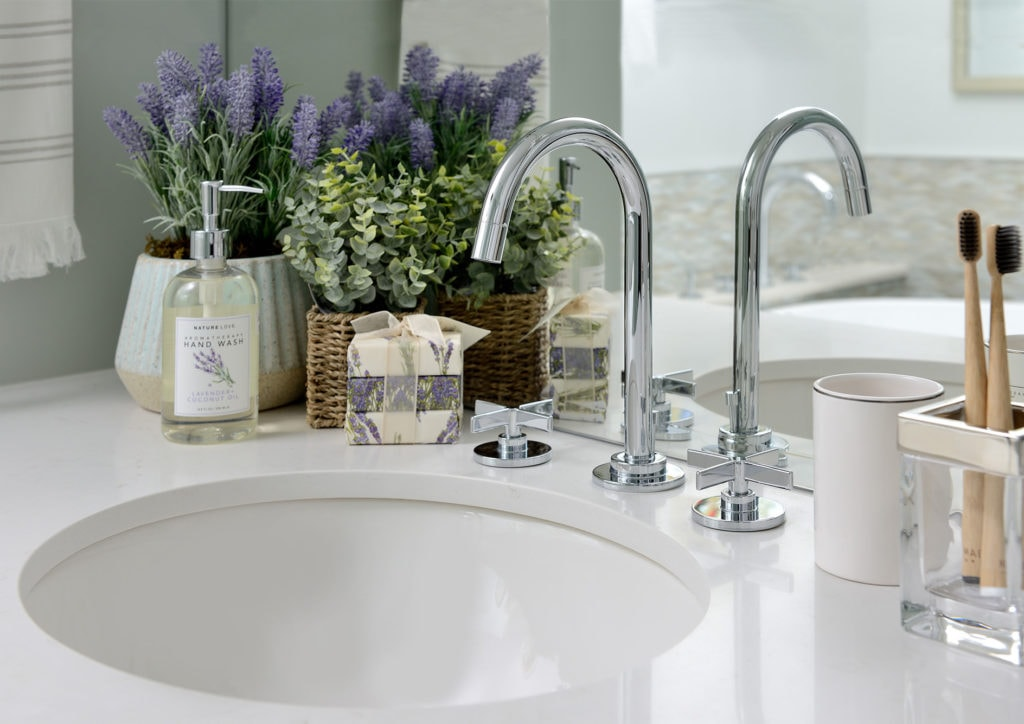 Bathroom sink with chrome faucet with cross/x handles and pretty lavender styling on countertop. Design by Judith Taylor Designs