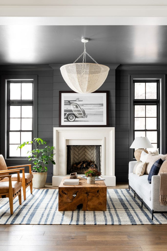 living room with black walls, white fireplace, and blue an dwhite plaid rug