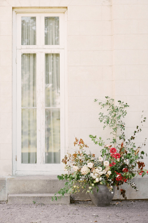 white stucco wall with a clay pot woth flowers