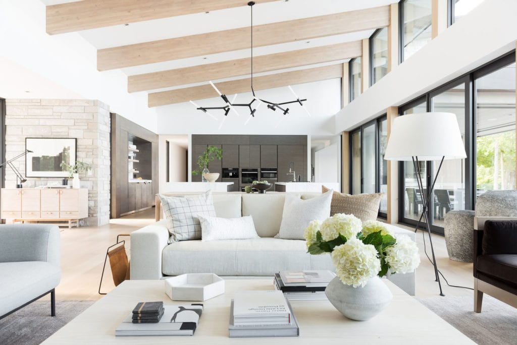 spaceous living roomw with bright light, and white furniture