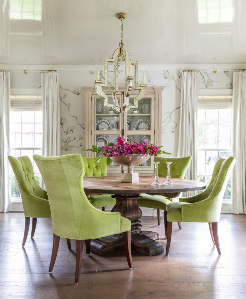 pretty dining room with apple green upholstered velvet chairs and traditional pedestal table