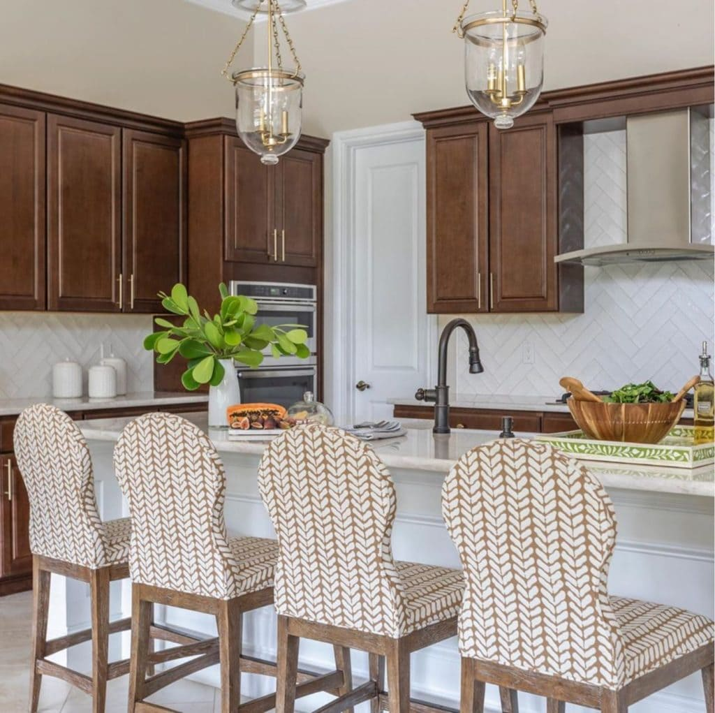 pretty kitchen with wood cabinets and white backsplash and beige and white counter chairs