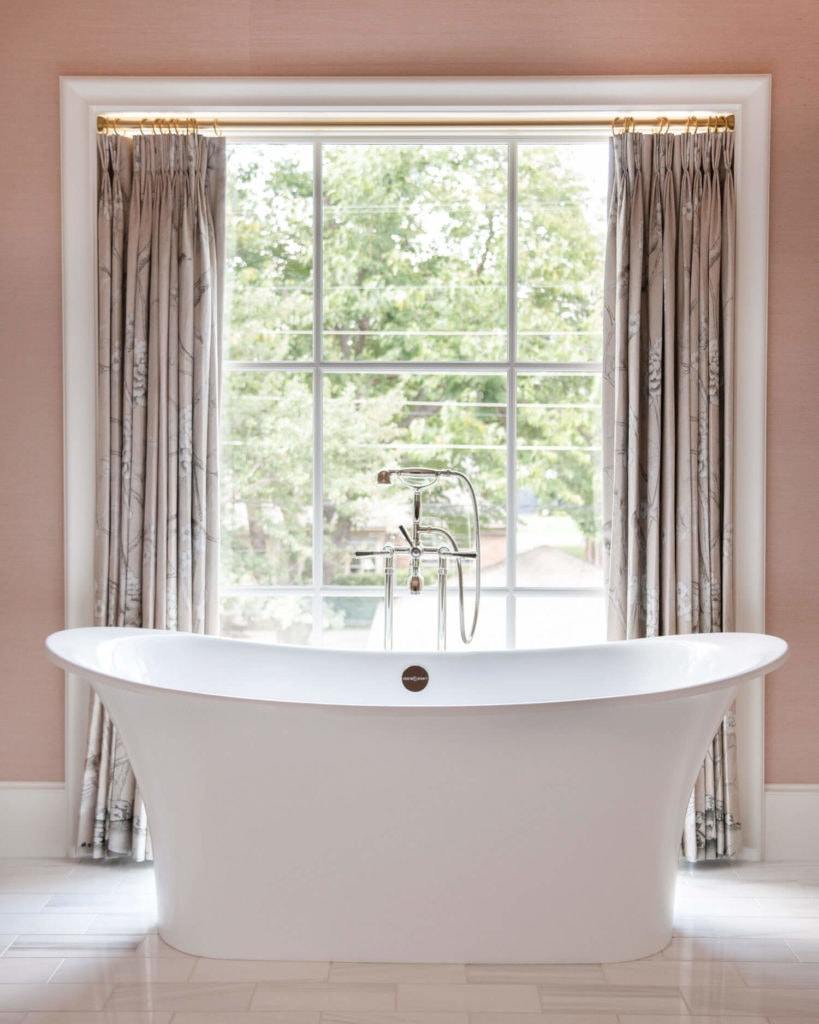 white tub against pink walls and pretty pink and white drapes