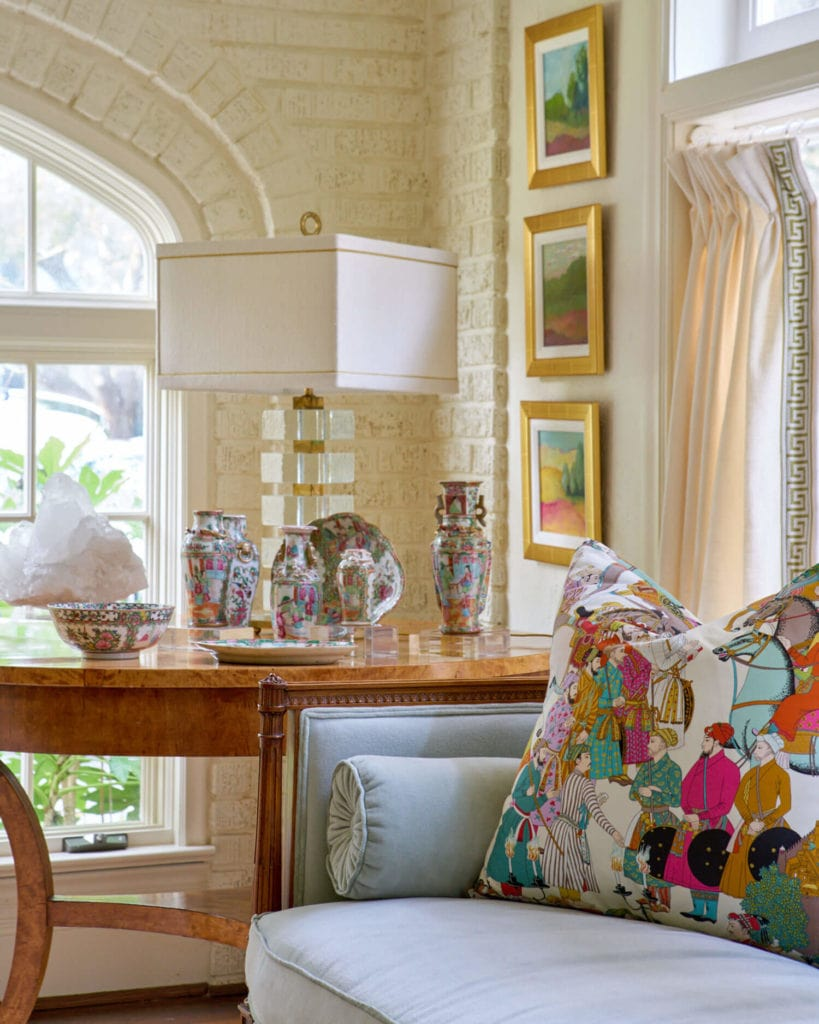 living room vignette with blue sofa, multicolour accent fabric on pillow and drapes depicting an asian scene
