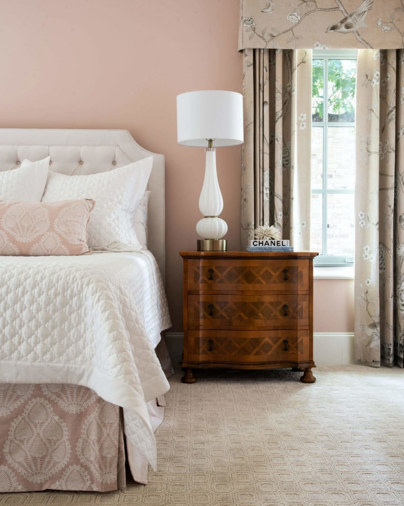 bedroom with chest of srawers night table, white beding and blush pink walls
