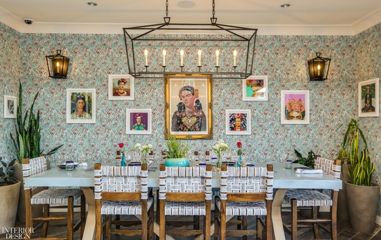 Gallery wall with Freida Kahlo inspired art on detailed wallpaper with dining table in front.
