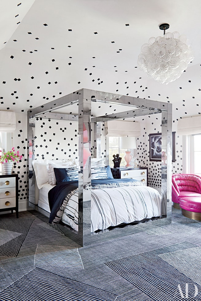 black and white bedroom wuth chrome canopy bed, and pink chair