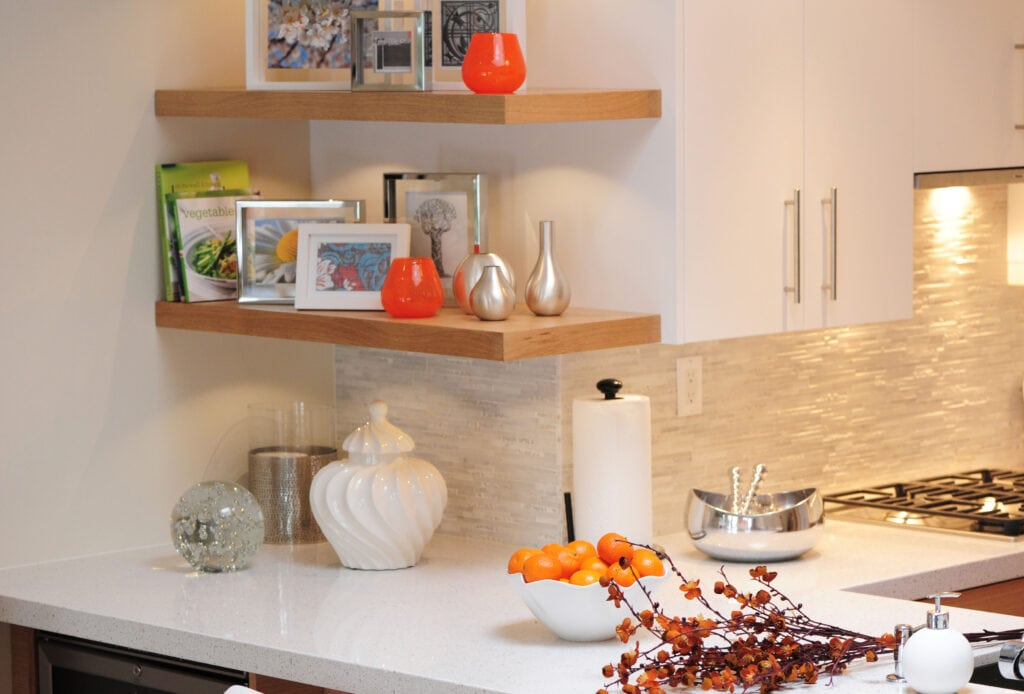 corner of kitchen with floating shelves and a textured backsplash with lighting.