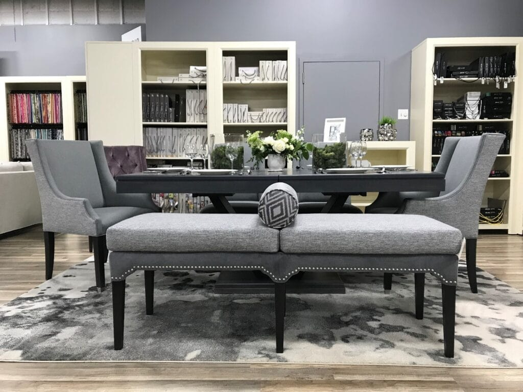 Dining room with grey end chairs and an upholstered grey bench with fabric sample books on shelves behind