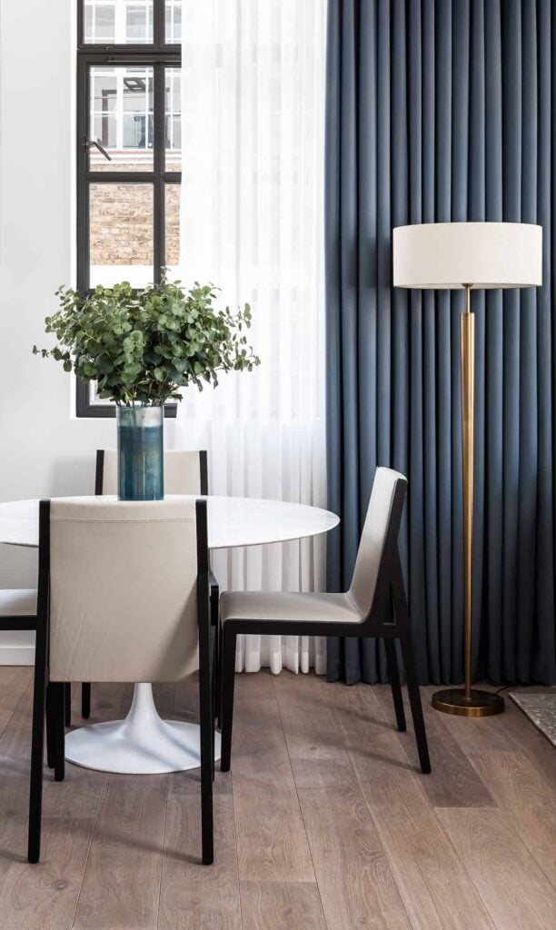 Modern round tulip table with chairs and floor lamp in front of window with white sheers and blue drapes.