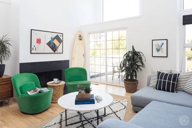 living room with green chairs blue sectional and white walls
