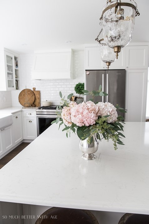 White kitchen with white cabinetr, white subway tiles and pink hydrangeas in the foreground