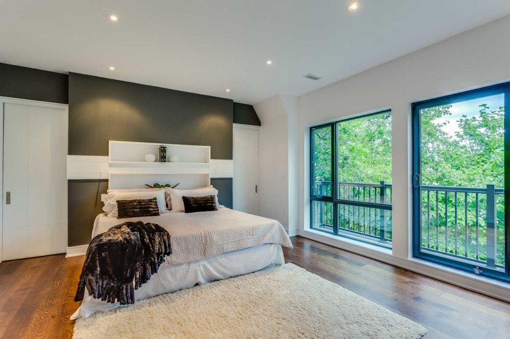 bedroom with feature wall with cast lighting and large picture windows