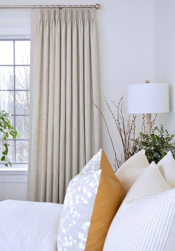 image of off white drapes with bed in front showing close-up of pillows