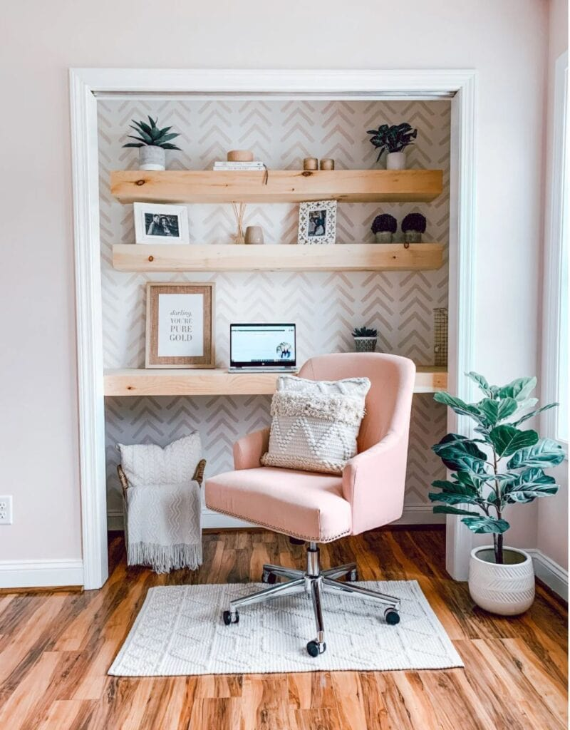 Closet converted to workspace with graphic wallpaper, wood shelves, and a pink desk chair