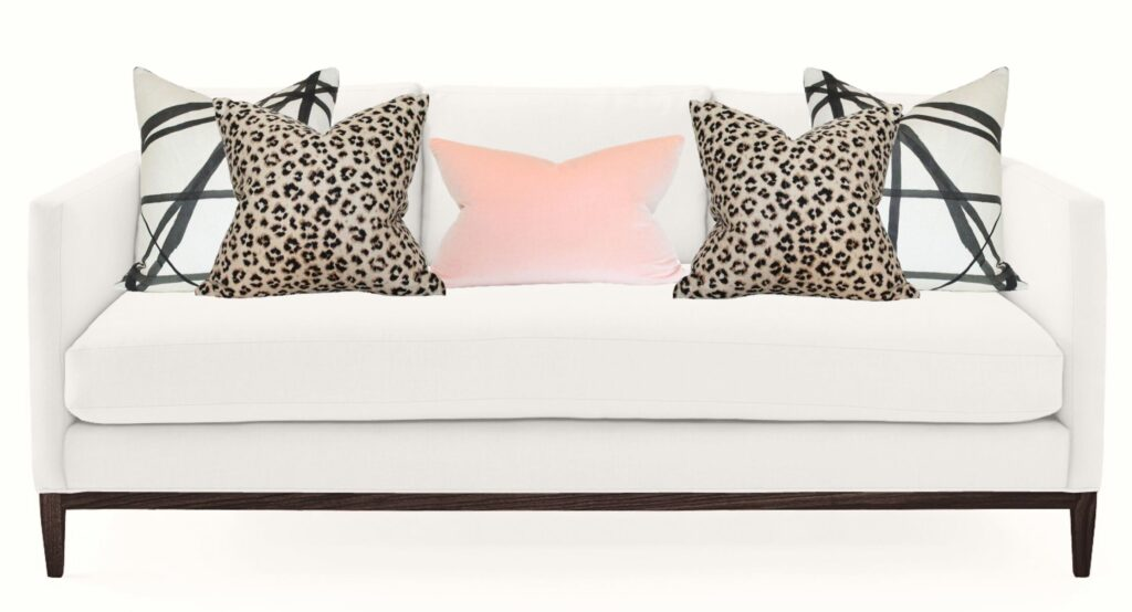 white sofa with geometric and animal print pillows and a pink one in the centre