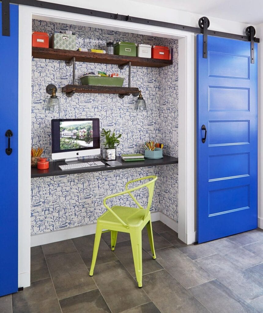 home office in a closet with blue and white wallpaper, floating shelves, a cobalt blue door, and citrus green chair