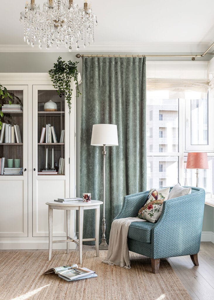 image of corner window with sage green drapes, a blue chair, and white built-in cabinets