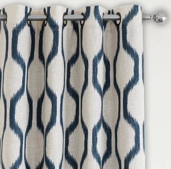 Teal pattern on linen ground drapery with grommets on a stainless steel rod