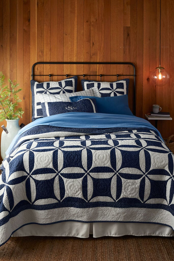 bed in cabin with blue and white quilt