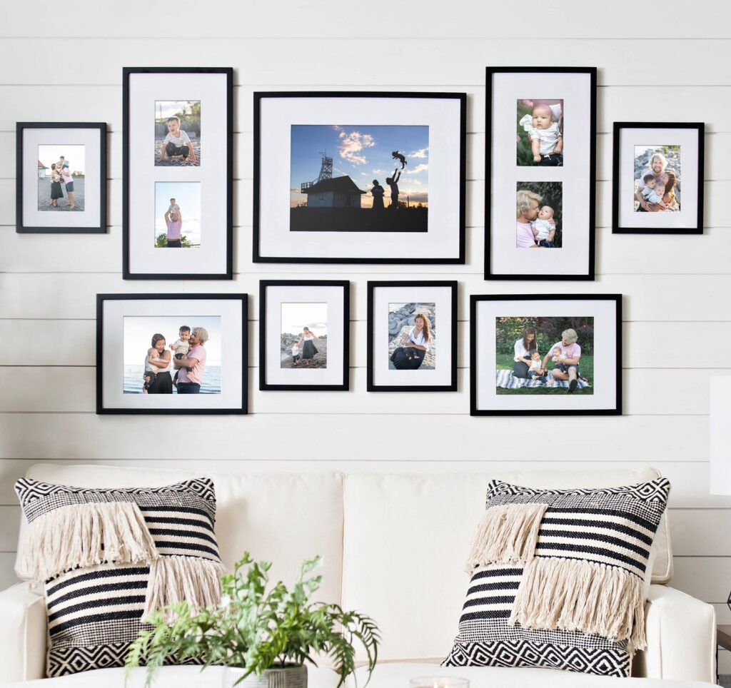 Gallery wall with black frames and family photos over a white sofa with graphic black and white pillows