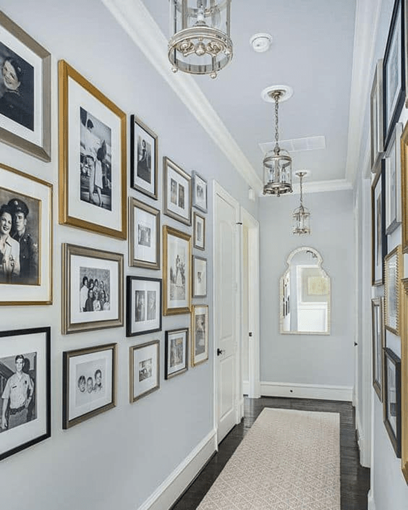 Classic hallway gallery wall with mirror at the end and lovely nickel lanterns.