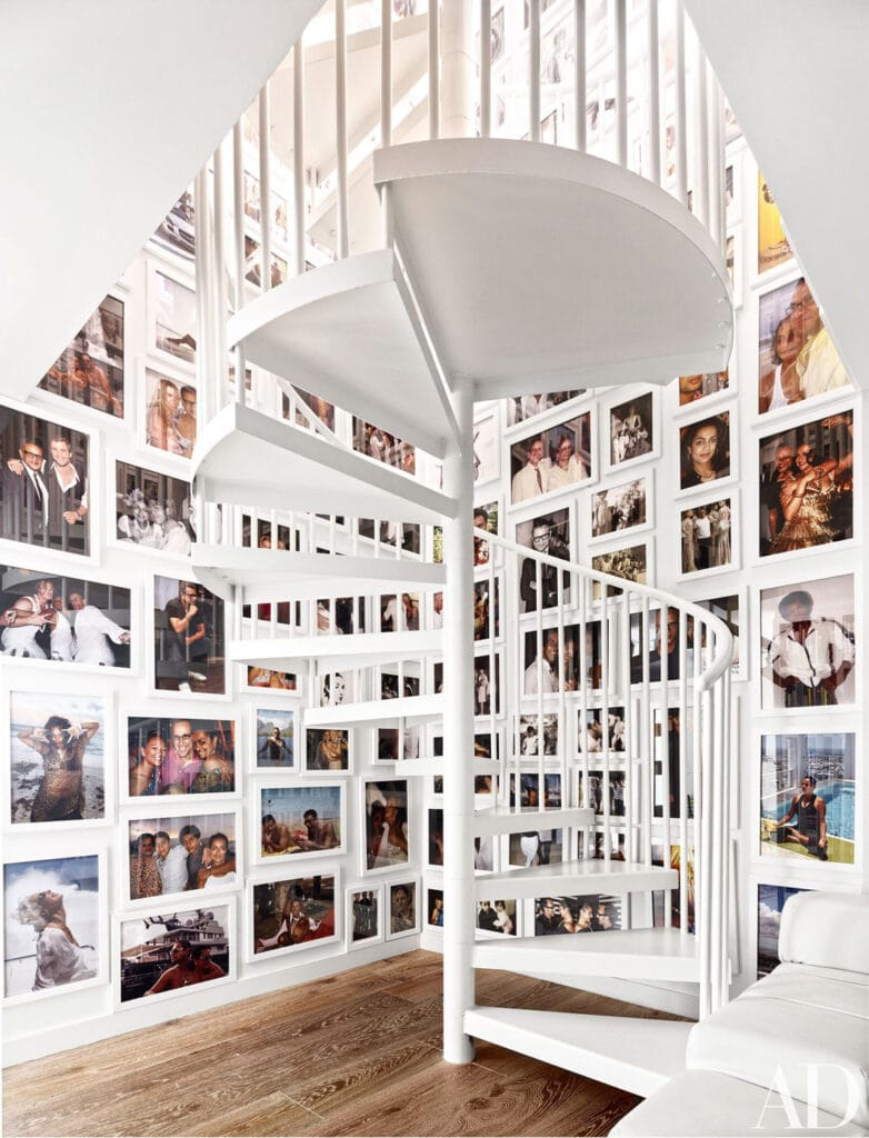 Spiral staircase with floor to ceiling framed photos in a gallery wall wrapping the stairwell