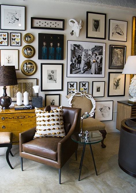 Eclectic gallery wall with framed art, photos, mirrors, and 3 dimensional objects (animal head with horns)