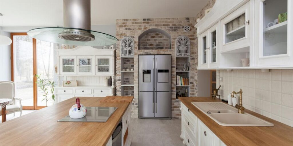 photo of a farmhouse kitchen with white cabinets and butcherblock countertops