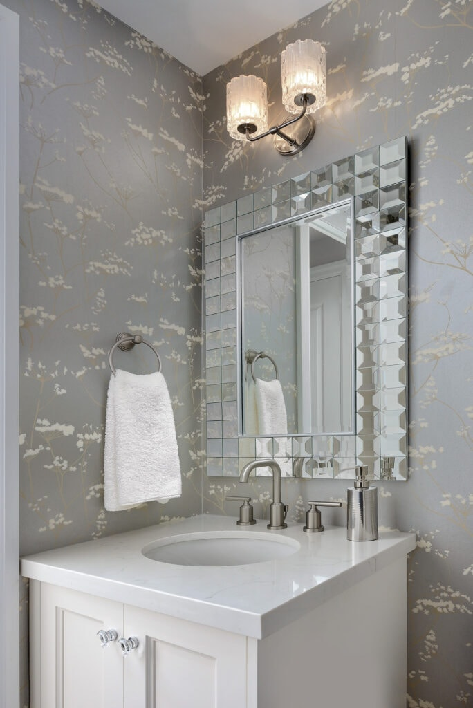 White vanity with silver wallpaper and a mirror with faceted mirror frame.