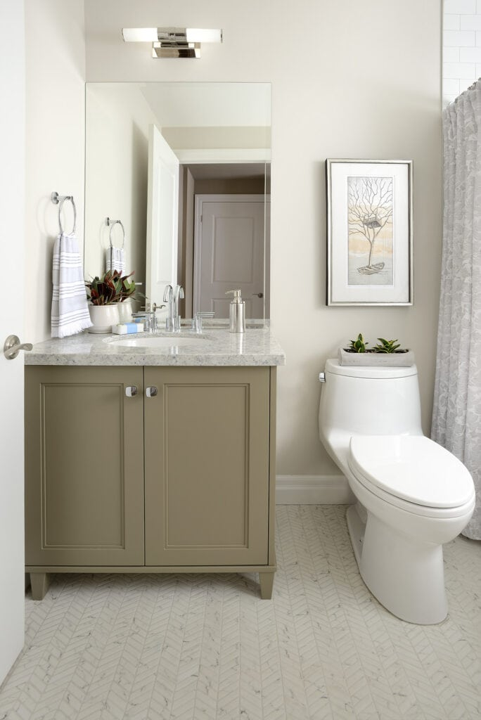 Bathroom photo of olive/taupe vanity with chevron tile on floor and art over the toilet. Design by Judith Taylor Designs