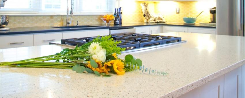 closeup picture of a beige countertop on a kitchen island with a cooktop, and cut flowers laying on the counter in the foreground